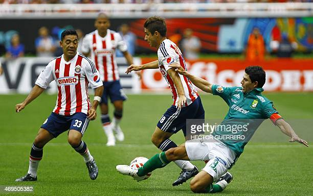Marco Fabian and Isaac Brizuela of Chivas vies of the ball with Jonny Magallon of Leon during their Mexican Clausura 2015 tournament football match...