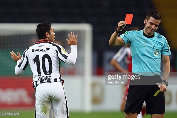 Marco Fabian of Frankfurt is sent off by referee Harm Osmers during the DFB Cup Second Round match between Eintracht Frankfurt and FC Ingolstadt at...
