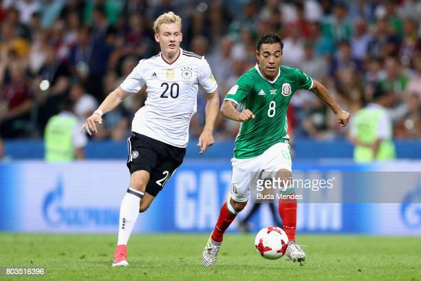 Marco Fabian of Mexico and Julian Brandt of Germany compete for the ball during the FIFA Confederations Cup Russia 2017 SemiFinal between Germany and...