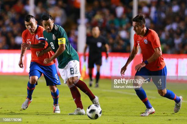 Marco Fabian of Mexico struggles for the ball against Mauricio Isla and Gary Medel of Chile during the international friendly match between Mexico...
