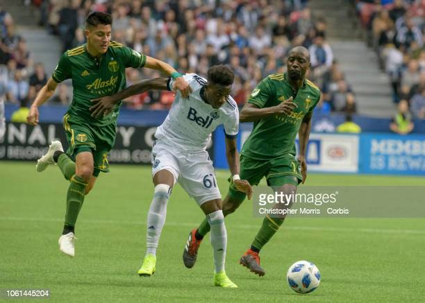 Marco Farfan of the Portland Timbers Alphonso Davies of the Vancouver Whitecaps #middle and Lawrence Olum of the Portland Timbers at BC Place on...