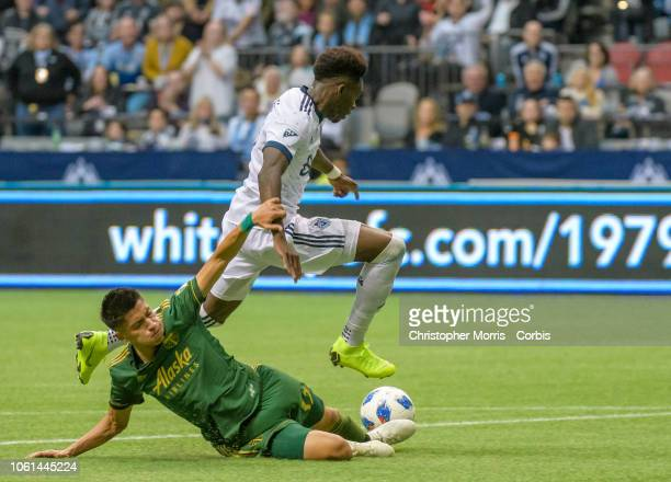 Marco Farfan of the Portland Timbers attempts to tackle Alphonso Davies of the Vancouver Whitecaps at BC Place on October 28 2018 in Vancouver Canada