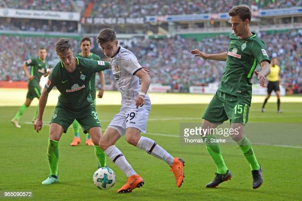 Marco Friedl and Sebastian Langkamp of Bremen tackle Kai Havertz of Leverkusen during the Bundesliga match between SV Werder Bremen and Bayer 04...