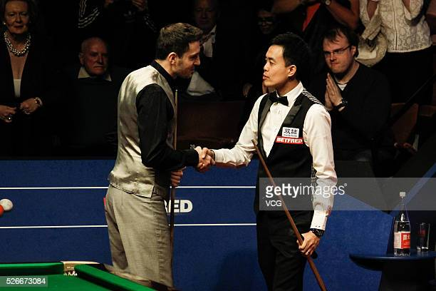 Marco Fu of Chinese Hong Kong shakes hands with Mark Selby of England in the semifinal on day fifteen of Betfred World Championship 2016 at The...
