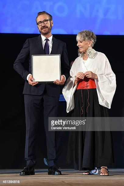 Marco Giallini receives the Nino Manfredi Award from Erminia Ferrari during the Nastri D'Argento Awards Ceremony 2014 on June 28 2014 in Taormina...