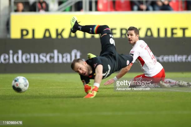 Marco Grüttner of Regensburg scores the opening goal against Robin Himmelmann, keeper of St. Pauli during the Second Bundesliga match between SSV...