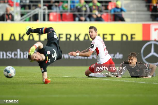 Marco Grüttner of Regensburg scores the opening goal against Robin Himmelmann, keeper of St. Pauli and his team mate Leo Östigard during the Second...