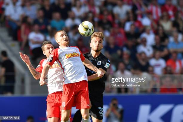Marco Gruettner and Kolja Pusch of Jahn Regensburg jump for a header with Marin Pongracic of 1860 Muenchen during the Second Bundesliga Playoff first...