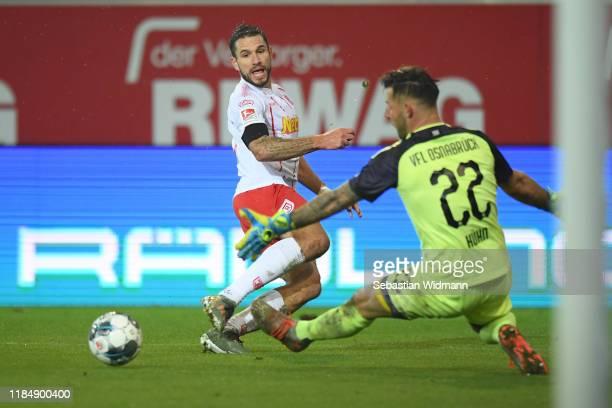 Marco Gruettner of Regensburg shoots the ball past Philipp Kuehn of Osnabrück during the Second Bundesliga match between SSV Jahn Regensburg and VfL...