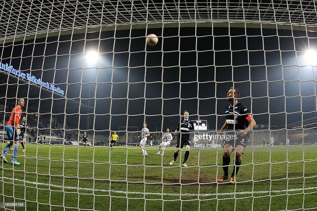 Marco Haller (C) of Aalen scores their first goal past goalkeeper Patric Klandt (L) and Bjoern Schlicke (R) of Frankfurt during the Second Bundesliga match between FSV Frankfurt and VfR Aalen at Frankfurter Volksbank Stadium on March 8, 2013 in Frankfurt am Main, Germany.