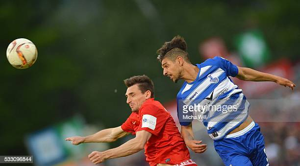 Marco Haller of Wuerzburg and Enis Hajri of Duisburg jump for a header during the Second Bundesliga Play Off first leg match between Wuerzburger...