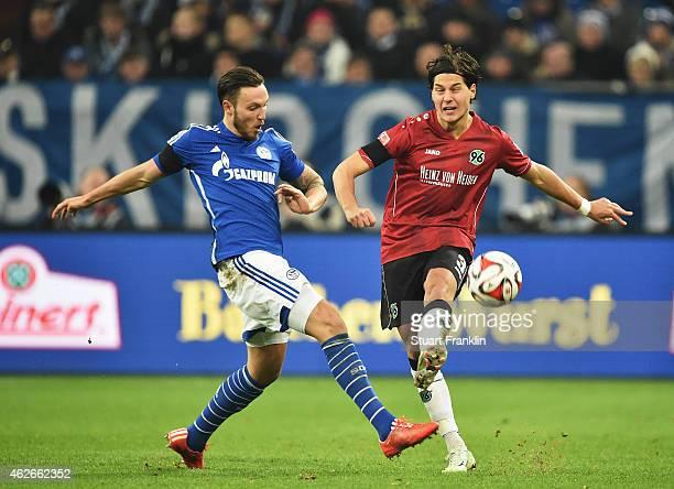 Marco Höger of Schalke is challenged by Miiko Albornoz of Hannover during the Bundesliga match between FC Schalke 04 and Hannover 96 at Veltins Arena...