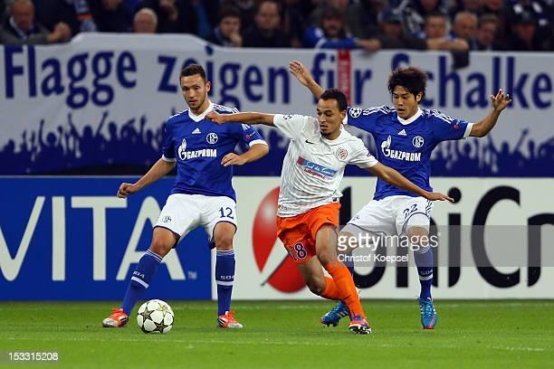 Marco Hoeger and Atsuto Uchida of Schalke challenge Karim AitFana of Montpellier during the UEFA Champions League group B match between FC Schalke 04...