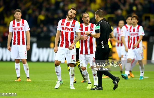 Marco Hoeger and team mate Matthias Lehmann discus with referee Patrick Ittrich of Koeln battle for the ball during the Bundesliga match between...