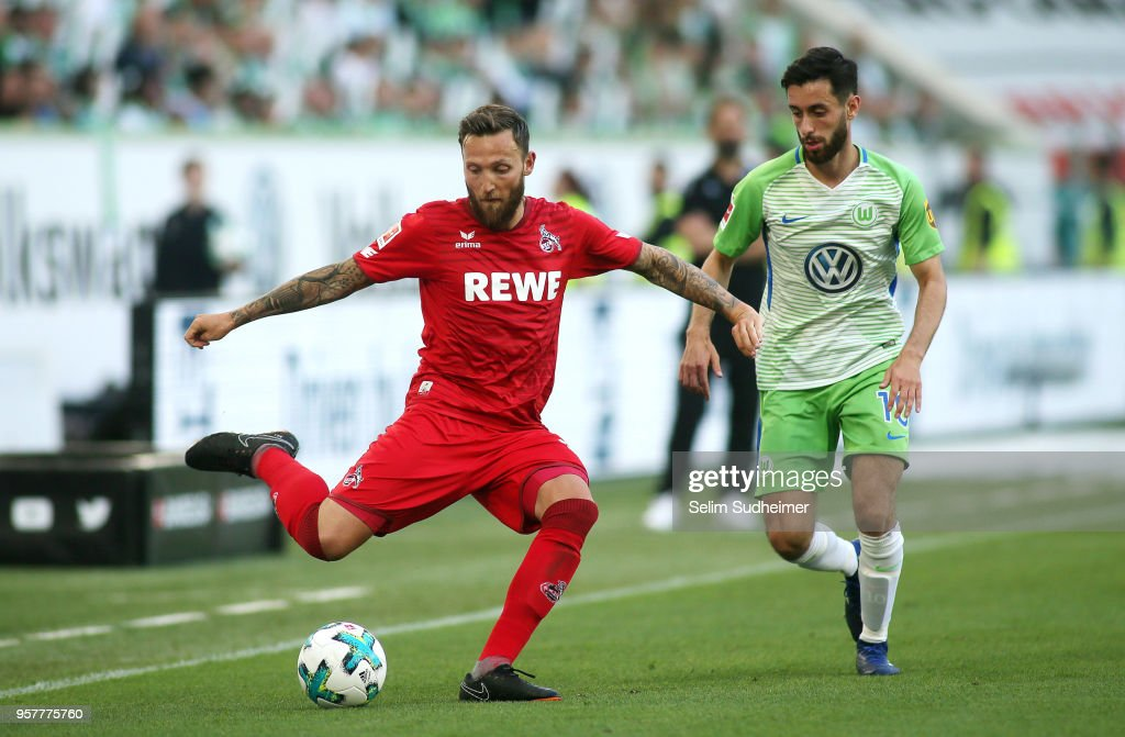 Marco Hoeger of Koeln (L) fights for the ball with Yunus Malli of Wolfsburgduring the Bundesliga match between VfL Wolfsburg and 1. FC Koeln at Volkswagen Arena on May 12, 2018 in Wolfsburg, Germany.