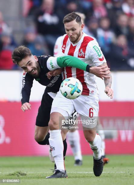 Marco Hoeger of Koeln is challenged by Kenan Karaman of Hannover during the Bundesliga match between 1 FC Koeln and Hannover 96 at...