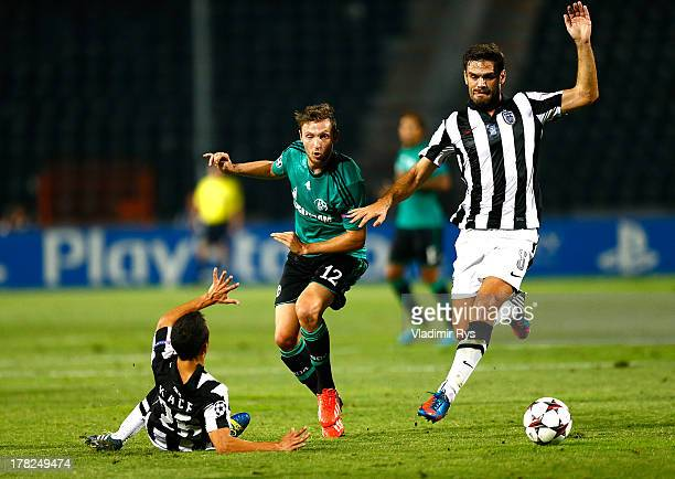 Marco Hoeger of Schalke attacks as Ergys Kace and Alexandros Tziolis of PAOK defend during the UEFA Champions League second leg play-off match...