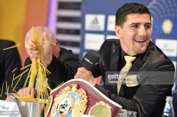 Marco Huck crushes spaghetti during the press conference at Lenkwerk on August 26 2014 in Bielefeld Germany The WBO World Championship Cruiserweight...