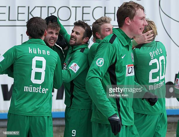 Marco Koenigs of Muenster jubilates with his team mates after scoring the second goal during the third league match between FC Hansa Rostock and...