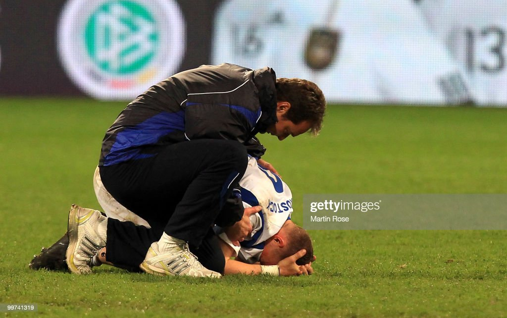Marco Kostmann (L), head coach of Rostock comforts Enrico Kern (R) of Rostock after the Second Bundesliga play off leg two match between Hansa Rostock and FC Ingolstadt 04 at DKB Arena on May 17, 2010 in Rostock, Germany. Hansa Rostock go down to the Third Bundesliga.