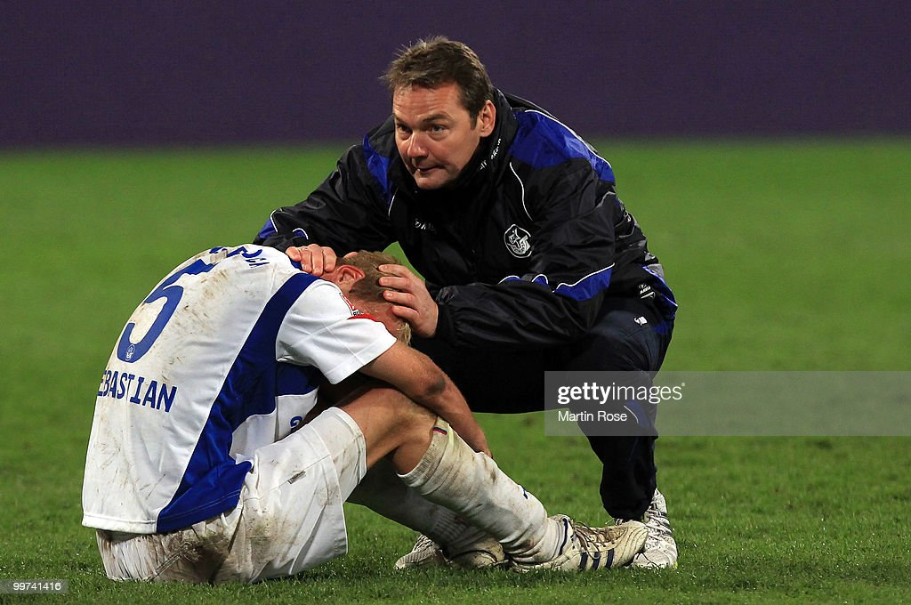 Marco Kostmann (R), head coach of Rostock comforts Tim Sebastian (L) of Rostock after the Second Bundesliga play off leg two match between Hansa Rostock and FC Ingolstadt 04 at DKB Arena on May 17, 2010 in Rostock, Germany. Hansa Rostock go down to the Third Bundesliga.