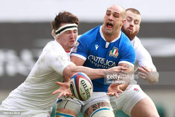 Marco Lazzaroni of Italy offloads the ball as Tom Curry and Luke Cowan-Dickie of England tackle during the Guinness Six Nations match between England...
