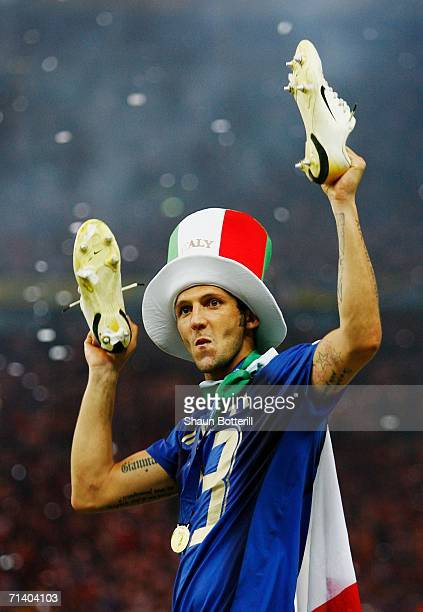 Marco Materazzi of Italy holds his boots aloft following his team's victory in a penalty shootout at the end of the FIFA World Cup Germany 2006 Final...