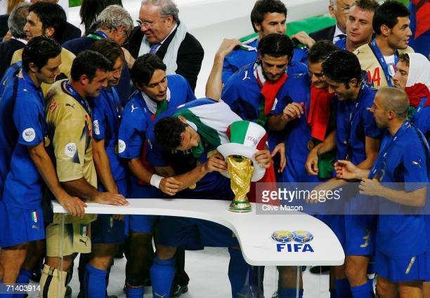 Marco Materazzi of Italy places an Italian hat on the World Cup trophy following victory in a penalty shootout at the end of the FIFA World Cup...