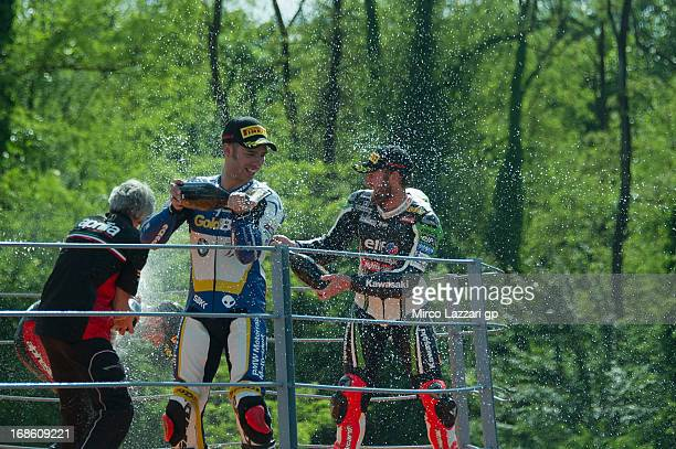 Marco Melandri of Italy and BMW Motorrad GoldBet SBK and Tom Sykes of Great Britain and Kawasaki Racing Team celebrate on the podium and spray...