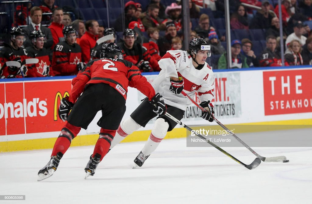 Marco Miranda #11 of Switzerland skates the puck up ice against Jake Bean #2 of Canada during the second period of play in the Quarterfinal IIHF World Junior Championship game at the KeyBank Center on January 2, 2018 in Buffalo, New York.