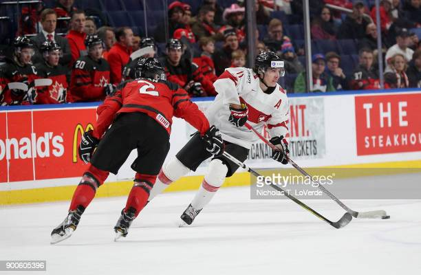 Marco Miranda of Switzerland skates the puck up ice against Jake Bean of Canada during the second period of play in the Quarterfinal IIHF World...