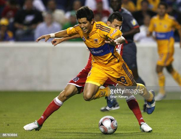 Marco Pappa of the Chicago Fire trips up Jesus Molina of Tigres UANL during the second half of the match in the SuperLiga 2009 soccer tournament at...
