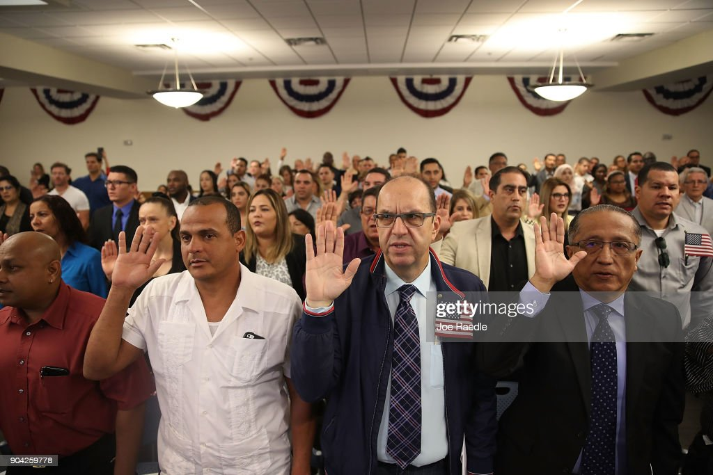 Marco Paranzino (C), orginally from Venezuela, and others become American citizens during a U.S. Citizenship & Immigration Services naturalization ceremony at the Hialeah Field Office on January 12, 2018 in Hialeah, Florida. 150 people from different countries around the world took part in the Oath of Allegiance.