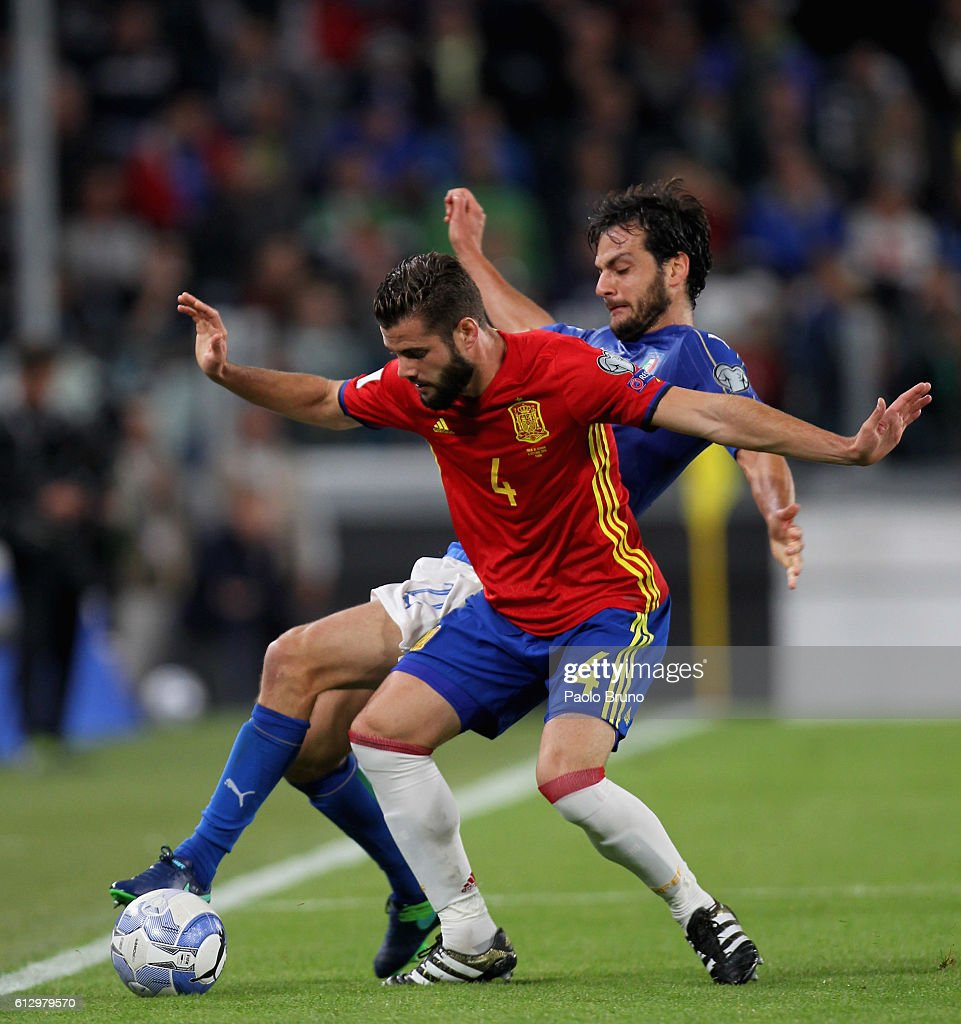 Marco Parolo of Italy competes for the ball with Nacho of Spain during the FIFA 2018 World Cup Qualifier between Italy and Spain at Juventus Stadium on October 6, 2016 in Turin.