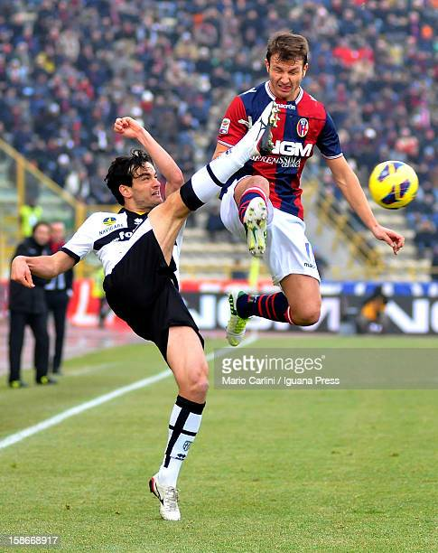 Marco Parolo of Parma FC competes for the ball with Marco Motta of Bologna FC during the Serie A match between Bologna FC and Parma FC at Stadio...