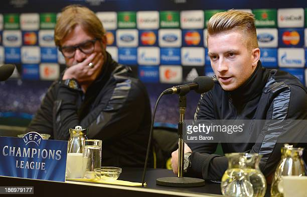 Marco Reus looks on next to head coach Juergen Klopp during a Borussia Dortmund press conference ahead of the UEFA Champions League Group F match...