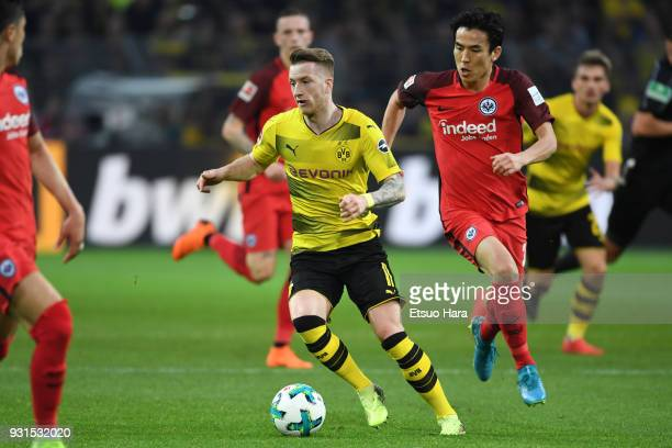 Marco Reus of Borussia Dortmund and Makoto Hasebe of Eintrackt Frankfurt compete for the ball during the Bundesliga match between Borussia Dortmund...