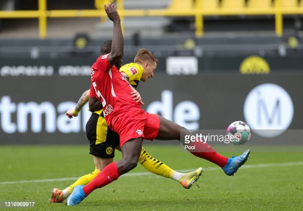 Marco Reus of Borussia Dortmund battles for possession with Dayot Upamecano of RB Leipzig during the Bundesliga match between Borussia Dortmund and...