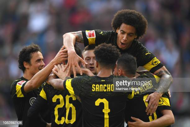 Marco Reus of Borussia Dortmund celebrates after scoring his team's third goal with his team mates during the Bundesliga match between VfB Stuttgart...