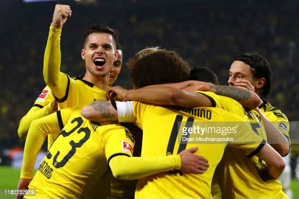 Marco Reus of Borussia Dortmund celebrates scoring his teams first goal of the game with team mates during the Bundesliga match between Borussia...