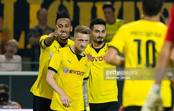 Marco Reus of Borussia Dortmund celebrates scoring the opening goal together with his team mates PierreEmerick Aubameyang and Ilkay Guendogan during...