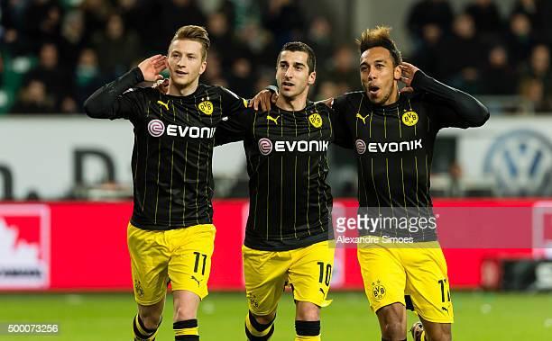 Marco Reus of Borussia Dortmund celebrates scoring the opening goal together with his team mates Henrikh Mkhitaryan and PierreEmerick Aubameyang...