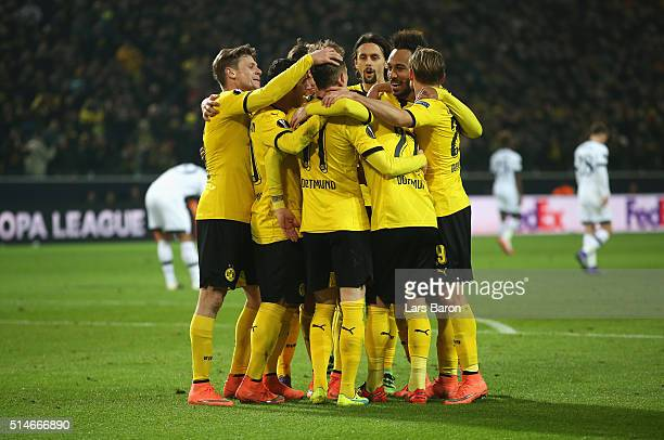 Marco Reus of Borussia Dortmund celebrates with team mates as he scores their third goal during the UEFA Europa League Round of 16 first leg match...