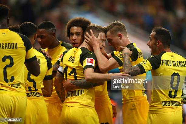 Marco Reus of Borussia Dortmund celebrates with teammates after scoring his team's second goal during the Bundesliga match between Bayer 04...