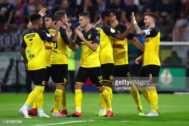Marco Reus of Borussia Dortmund celebrates with teammates after scoring his team's first goal during the DFB Cup first round match between KFC...