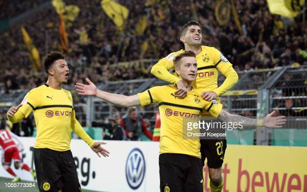 Marco Reus of Borussia Dortmund celebrates with teammates Christian Pulisic and Jadon Sancho after scoring his team's third goal during the DFB Cup...