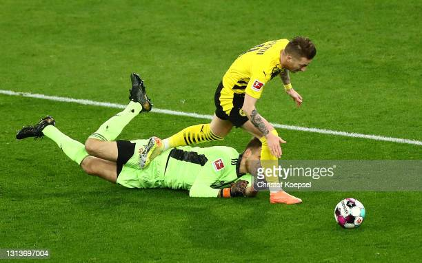 Marco Reus of Borussia Dortmund is challenged by Andreas Luthe of 1. FC Union Berlin leading to a penalty being awarded during the Bundesliga match...