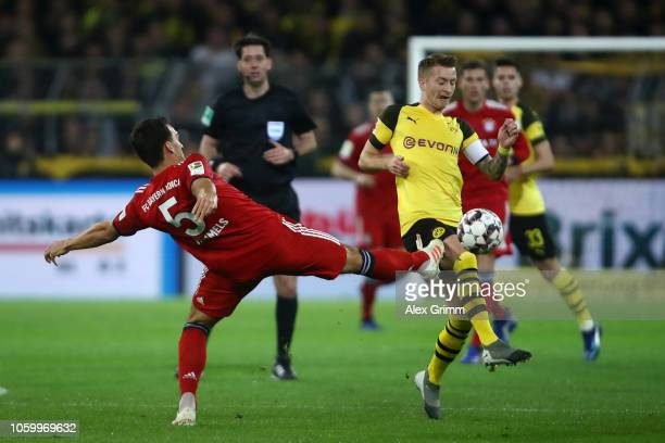 Marco Reus of Borussia Dortmund is challenged by Mats Hummels of Bayern Munich during the Bundesliga match between Borussia Dortmund and FC Bayern...