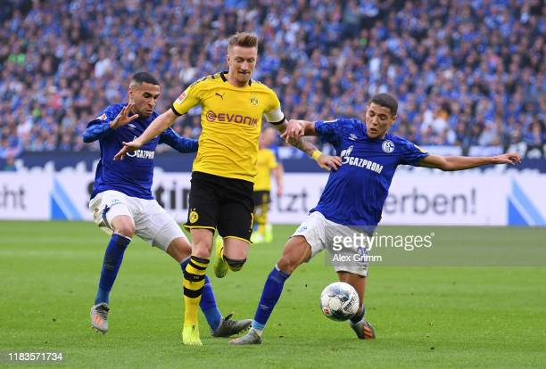Marco Reus of Borussia Dortmund is challenged by Omar Mascarell of FC Schalke 04 and Amine Harit of FC Schalke 04 during the Bundesliga match between...