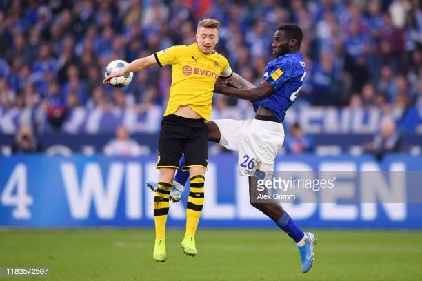Marco Reus of Borussia Dortmund is challenged by Salif Sane of FC Schalke 04 during the Bundesliga match between FC Schalke 04 and Borussia Dortmund...